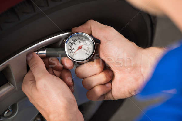 Mechanic Checking Air Pressure Level In Car Tire Stock photo © AndreyPopov