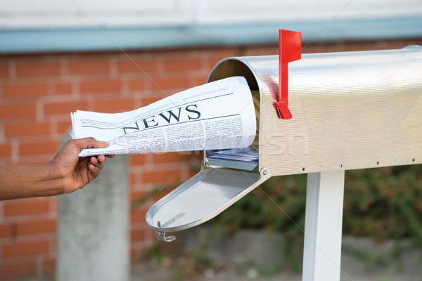 Person's Hand Opening Mailbox To Remove Newspaper Stock photo © AndreyPopov