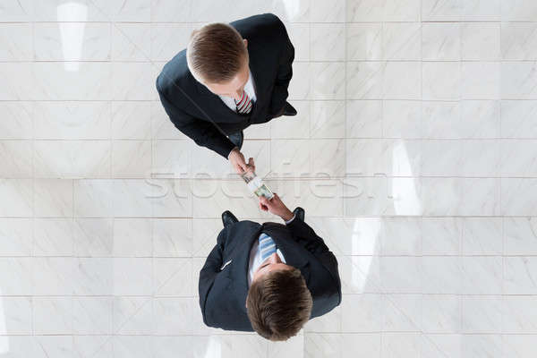 Businessman Bribing Colleague In Office Stock photo © AndreyPopov