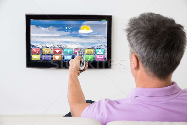 Man On Sofa Using Remote Control In Front Of TV Stock photo © AndreyPopov