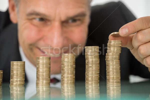 Businessman Placing Coin Over Stack Of Coins At Desk Stock photo © AndreyPopov