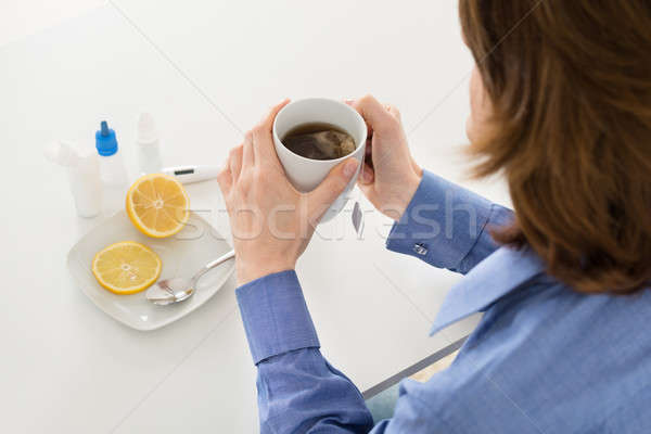 Sick Woman Holding Cup Of Tea Stock photo © AndreyPopov