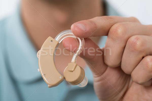Férfi tart hallókészülék közelkép kéz otthon Stock fotó © AndreyPopov