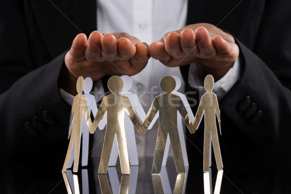 Businessperson Protecting Cut-out Figures Stock photo © AndreyPopov
