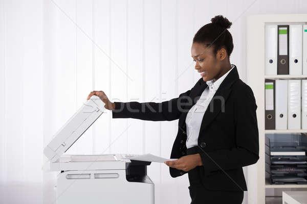 Smiling Businesswoman Using Photocopy Machine Stock photo © AndreyPopov