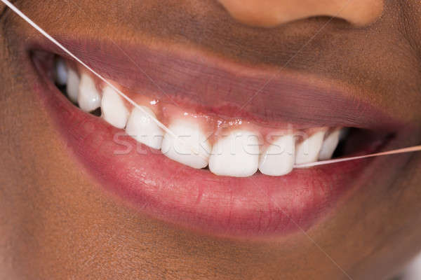 African Woman Flossing Teeth Stock photo © AndreyPopov