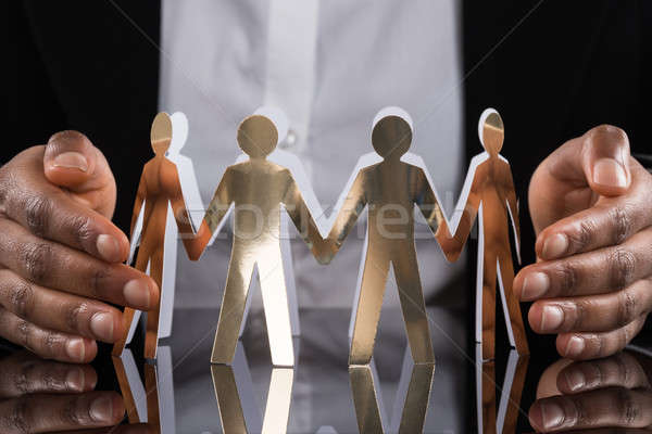 Stock photo: Businessperson Protecting Cut-out Figures