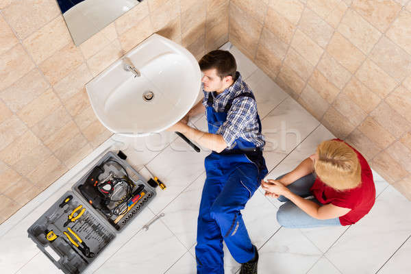 Stock photo: Young Male Plumber Fixing Sink In Bathroom