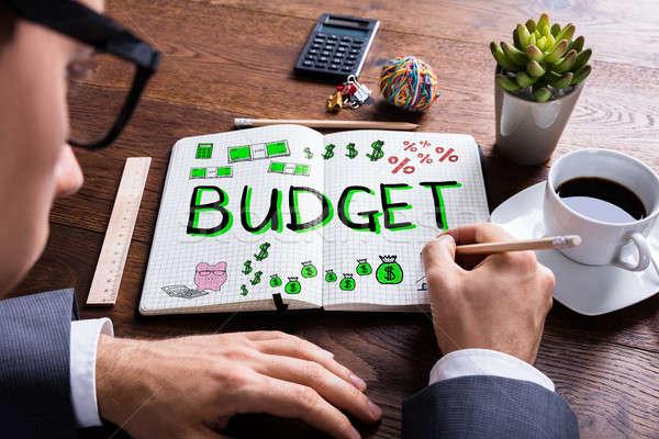 Homem desenho orçamento plano caderno secretária Foto stock © AndreyPopov
