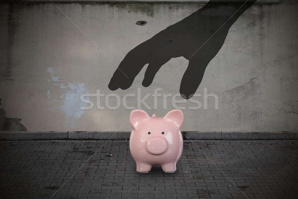 Silhouette Hand Picking Up Piggy Bank On Street Stock photo © AndreyPopov