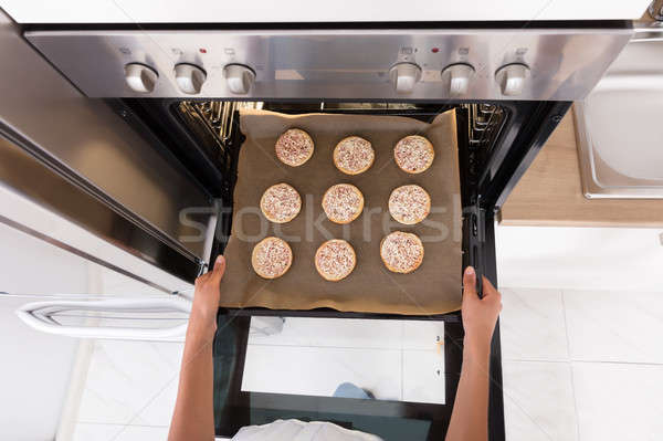 Human Hand Baking Cookies In Microwave Oven Stock photo © AndreyPopov