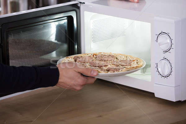 Human Hand Baking Pizza In Microwave Oven Stock photo © AndreyPopov