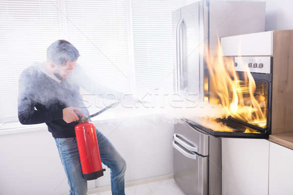 Man Using Fire Extinguisher To Stop Fire Coming From Oven Stock photo © AndreyPopov