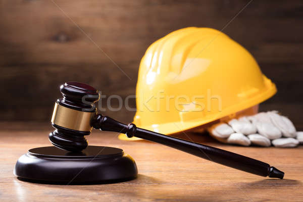 Gavel In Front Of Yellow Safety Helmet Stock photo © AndreyPopov