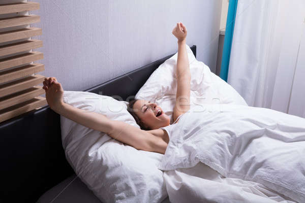 Woman Stretching Her Hands On Bed Stock photo © AndreyPopov