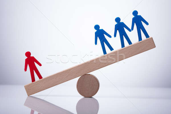 Red Human Figure Standing Against Team On Seesaw Stock photo © AndreyPopov