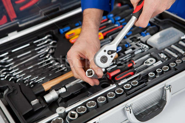 Portrait of automechanic taking a wrench out of toolbox Stock photo © AndreyPopov