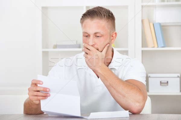Businessman reacting in shock to a letter Stock photo © AndreyPopov