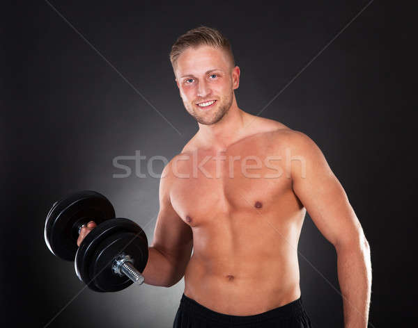 Young man working out lifting weights in a gym Stock photo © AndreyPopov