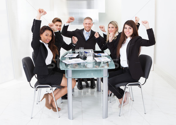 Sikeres üzleti csapat karok a magasban portré ül asztal Stock fotó © AndreyPopov