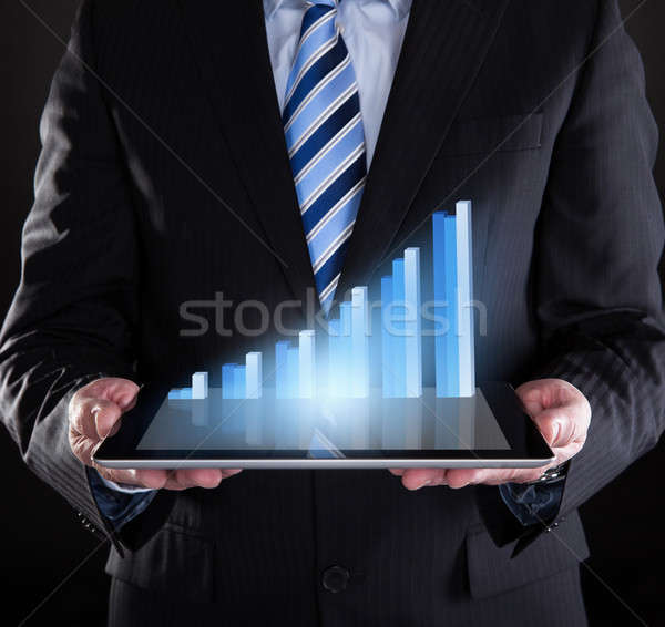 Businessman Holding Digital Tablet With Graph Stock photo © AndreyPopov