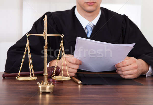 Judge Reading Document At Table In Courtroom Stock photo © AndreyPopov