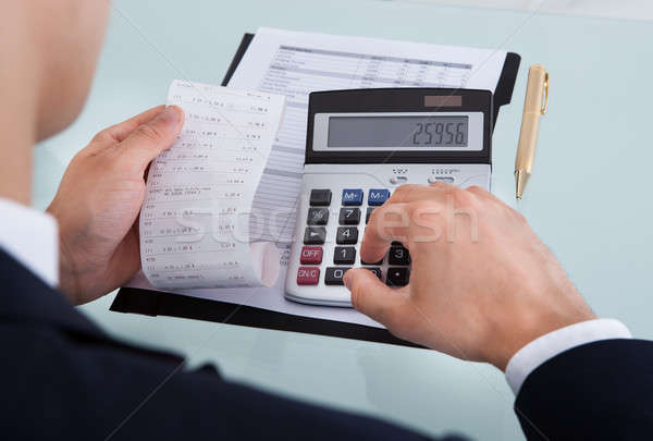 Stock photo: Businessman Holding Receipt While Calculating Expense In Office