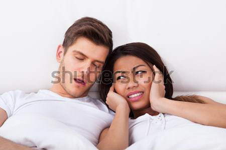 Irritated Woman Covering Ears While Man Snoring In Bed Stock photo © AndreyPopov