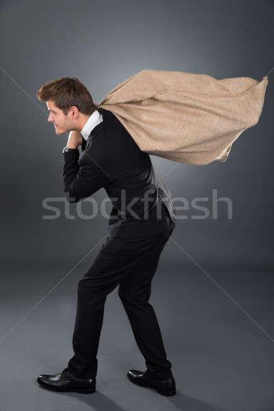 üzletember hordoz pénzeszsák teljes alakos szürke pénz Stock fotó © AndreyPopov