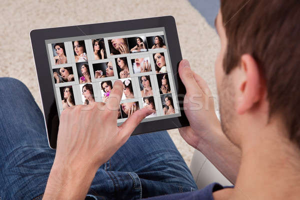 Man Browsing Pictures On Digital Tablet Stock photo © AndreyPopov