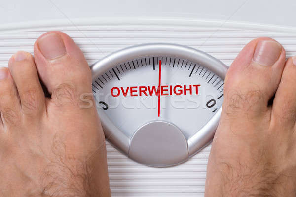 Feet On Weight Scale Indicating Overweight Stock photo © AndreyPopov