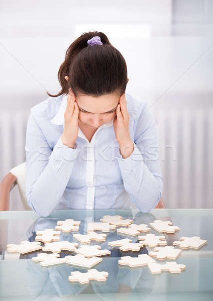 Businesswoman With Puzzle At Desk Stock photo © AndreyPopov