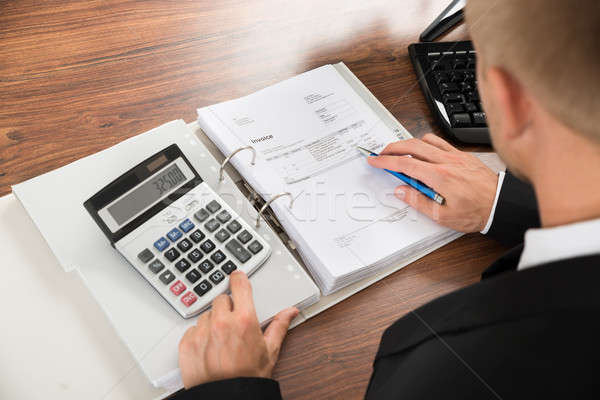 Businessman Calculating Invoice At Desk In Office Stock photo © AndreyPopov