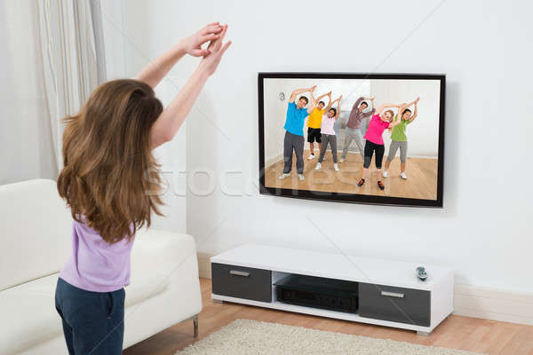 Girl Doing Exercise At Home Stock photo © AndreyPopov