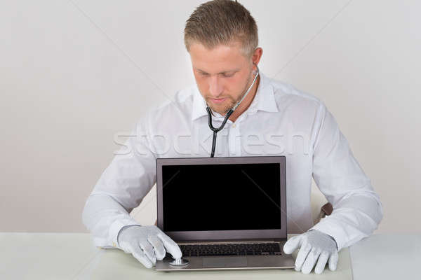 Technician Examining Laptop With Stethoscope Stock photo © AndreyPopov