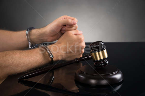 Person Hand In Handcuffs At Desk Stock photo © AndreyPopov