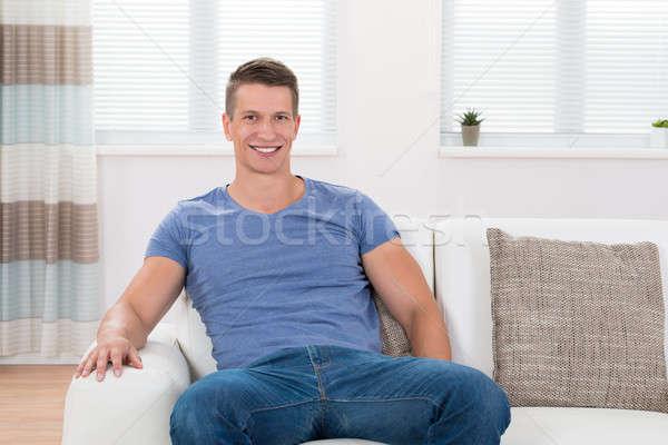 Homme séance canapé salon jeunes heureux Photo stock © AndreyPopov