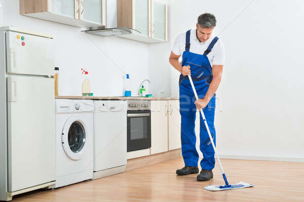 Worker Mopping Floor In Kitchen At Home Stock photo © AndreyPopov