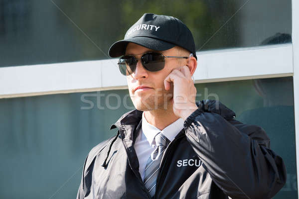 Young Security Guard Standing In Front Of The Entrance Stock photo © AndreyPopov
