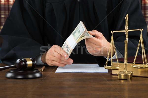 Corrupt Judge Holding Dollar Bundle At Desk Stock photo © AndreyPopov