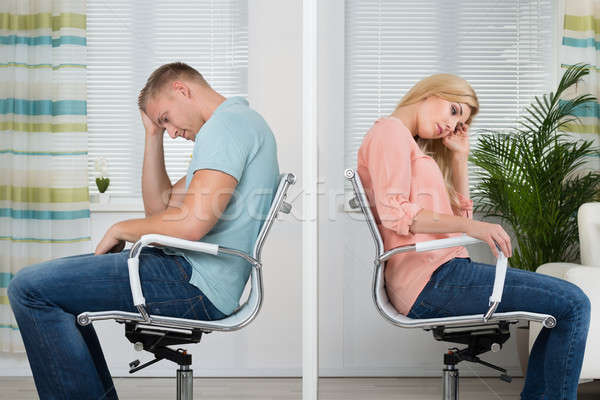 Upset Couple Sitting On Chairs At Home Stock photo © AndreyPopov