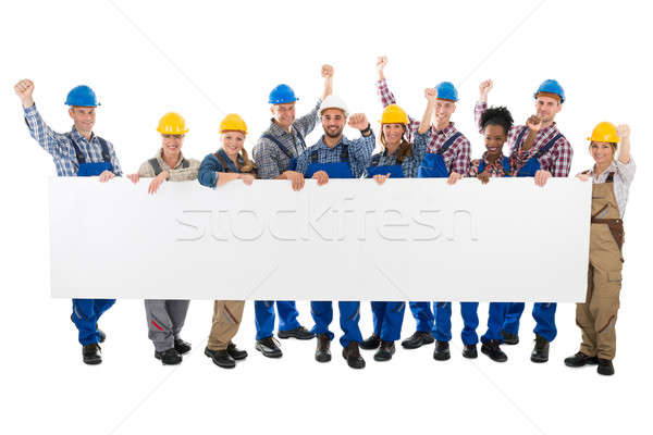 Happy Carpenters With Arms Raised Holding Blank Billboard Stock photo © AndreyPopov