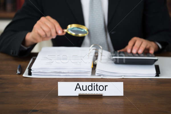 Auditor Scrutinizing Financial Documents In Office Stock photo © AndreyPopov