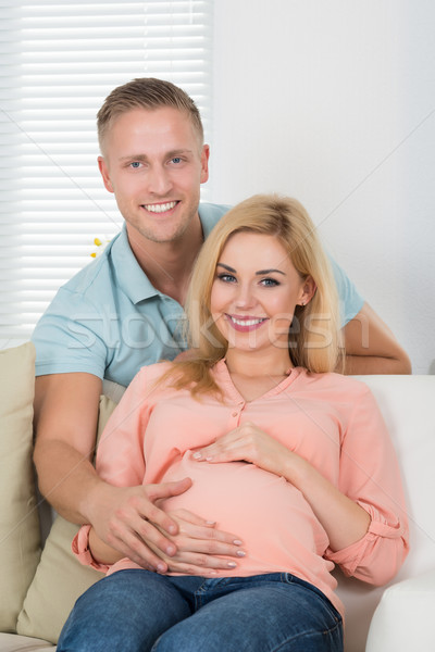 Happy Expecting Couple Sitting On Sofa At Home Stock photo © AndreyPopov
