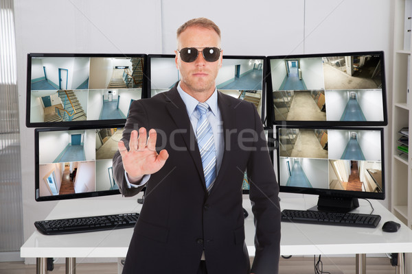 Security Manager Gesturing Stop Sign Against Monitors Stock photo © AndreyPopov