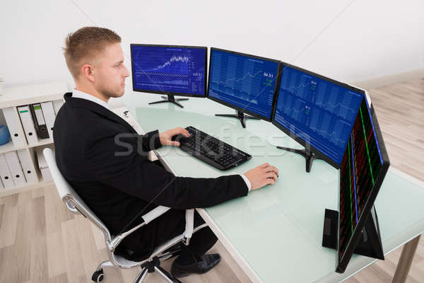 Empresário olhando gráfico tela do computador jovem múltiplo Foto stock © AndreyPopov