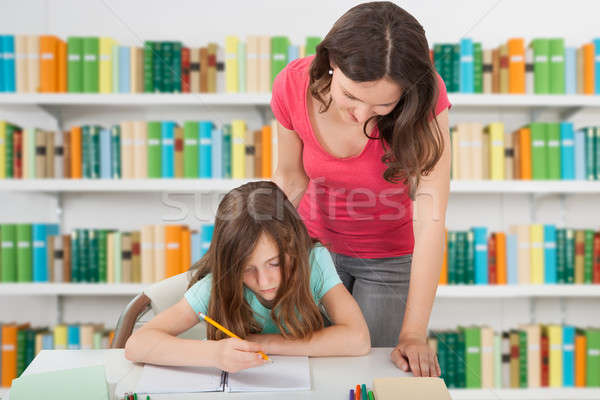 Teacher Assisting Girl At School Library Stock photo © AndreyPopov
