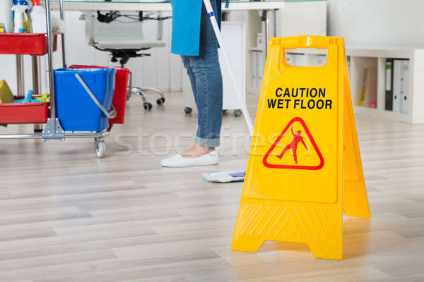 Female Janitor Mopping Wooden Floor With Caution Sign Stock photo © AndreyPopov