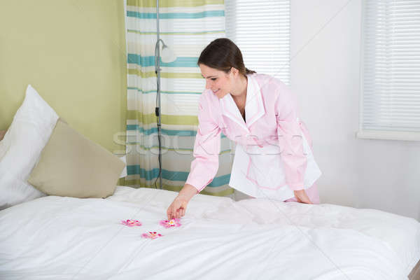 Female Housekeeper Decorating Bed With Flowers Stock photo © AndreyPopov