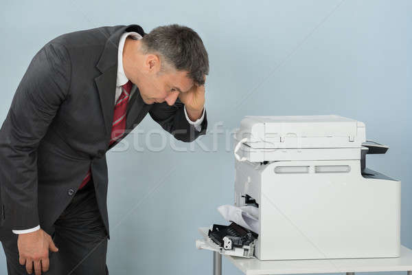 Businessman Looking At Printer Machine At Office Stock photo © AndreyPopov